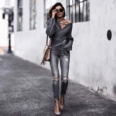 Erica Hoida is wearing a wrap-front cardigan, tied around the waist to accentuate her silhouette. She pairs this piece with skinny, distressed jeans, chunky jewellery and stilettos. Brands not specified.