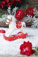Kleines Deko-Schaukelpferd, Fliegenpilz und Rosenblüten auf Kunstschnee
