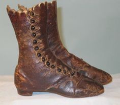 "High Button Boots, c1860-1865; Dark brown leather, stacked wood heel, 26 glass shoe buttons, cream cotton twill lining. Measurements: L, 9""; W, 2.4""; Heel, 1""; Ht, 8.5"".  Comments: Dating to the 1860s, these lady's high button walking boots have the rounded square toes and  narrow waist soles typical of 1860s fashionable footwear."