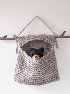 Free knitting pattern for Toy Hideaway Hanging Bag - This adorable pattern is knit in garter stitch and folded around a stick or a branch. The pattern is in German but you can translate by opening the page in the Chrome browser, right clicking on the text on the page and selecting Translate to English. However, you can probably easily figure it out without translation.