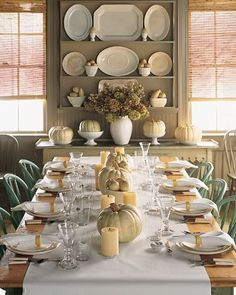 Neutral Thanksgiving tablescape. White linens and dinnerware with cream napkin rings and candles for accent. Earthy white pumpkins for centerpieces.
