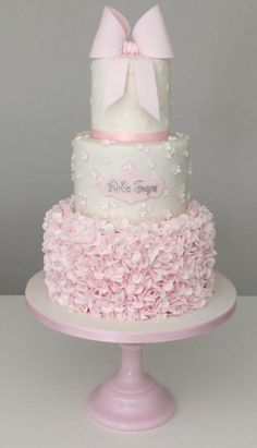 "This three tier christening cake in delicate pink and white featured ruffles, blossoms, polka dots and a touch of sparkle, topped with an icing bow. Visit our facebook page for more photos. """":http://www.facebook.com/TiersTiaras"