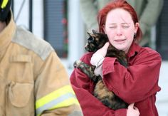 Erin Jessup crying, holding a cat firefighters rescued from her burning home in Berryville, Virginia.