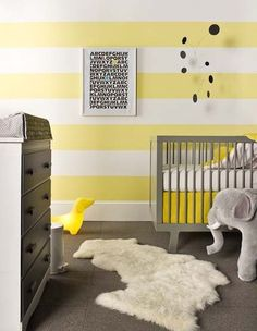 Gray and yellow nursery, yellow and white striped walls, fur rug, modern nursery