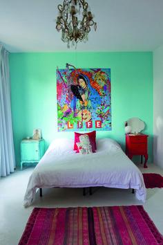 Arte Variopinto : El cuarto principal hace de los colores un recurso imbatible. Sobre la pared de fondo pintada en color aqua, la Obra da la nota pop-art. En el centro, un sommier, con edredón y almohadones en color rojo intenso, custodiado por un par de mesas de estilo francés  pintadas en rojo y turquesa. La luz general la da una araña con caireles que propone un contraste de estilos con la colorida alfombra com…