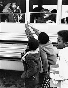 Both Caucasian and African American school children enter the White Hills School as part of an experimental desegregation program in Berkeley, California. African American children were bused in from a neighboring area. April 1964.