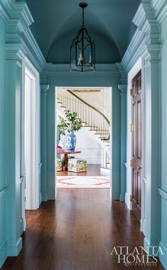 Atlanta Homes & Lifestyles From a beautiful turquoise blue hallway we have a peek into the foyer with a dramatic blue and white Chinese porcelain vase. SaveSave