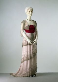 Around 1910, leading fashion houses such as Worth created evening dresses with a straight silhouette. Their impact depended on the juxtaposition of colours and a variety of luxurious and richly decorated fabrics. On this garment, vivid velvet pile is set against light-reflecting beadwork, and the triple-tiered matt net overskirt covers the sheen of the trained satin skirt. The pillar-like look exemplified by this dress replaced the exaggerated curves of the early 1900s.