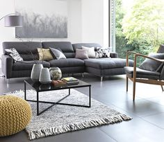Large grey corner sofa in living room area with scatter cushions and yellow knitted footstool.