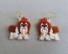 These cute little earrings depict an adorable little Mermaid with blue fins and ginger-red hair . They measure 5/8 wide and are 1-5/8 long, excluding the ear wires and are woven using the brick stitch and approximately 388 tiny seed beads. Although some people find bead work tedious, I really love it. There is something so fascinating about stitching the beads in place, one by one and watching the picture develop.  They would make a great gift or maybe a treat for yourself!  The pierced…