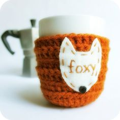 "Hand embroidered ""Foxy"" in light brown cotton thread on real wool felt cream patch, sewn on handmade burnt orange acrylic crochet coffee mug tea cup cozy. Are you foxy"