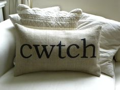 Burlap (hessian) pillow / cushion cover with the Welsh word CWTCH printed by hand in black lettering on the front. Cwtch is the Welsh word for cuddle and is used daily by most Welsh people (even the English speaking ones like me!).  This would be a great gift for someone of Welsh heritage now living overseas as a reminder of home.  Measures 12 x 20 (insert not included).  Spot clean or specialist clean only - burlap (hessian) cannot be washed.  *** Please read the description of the item…