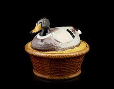 Terrina com tampa em forma de pato sobre cesto em cerâmica da Secla.