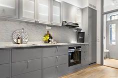 Vackert grått kök från Ballingslöv med integrerade vitvaror från Siemens. Lyxig känsla med bänkskiva samt väggar i Carrara-marmor. Gott om bra förvaring i både över- och underskåp med belysning under samt generöst med eluttag. Öppen social planlösning mellan kök och vardagsrum.