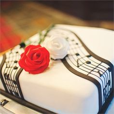 """The newlywed couple cut through a 10"""" square fruit filled wedding cake that had been decorated with white icing and featured a couple of iced roses and a stave of music.The Cake Gallery in Kings Norton, Birmingham had designed the cake specifically for the bride and groom and was given to guests in small bags to take home with them at the end of the evening.Zoe and Philip are keen cruisers and have booked to travel on the Crown Princess, through Princess Cruises from Southampton later in…"""