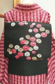 シックな黒の地に、愛らしいフランボワーズピンクと白、品の良い華やぎ香る金と銀で織り出された雛菊のような花模様が可憐な開き名古屋帯です。