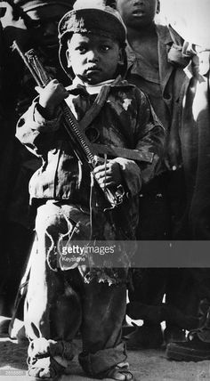 1976: A child soldier of the Marxist MPLA in battledress holding a sten gun during the civil war in Angola.