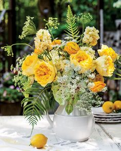 Vibrant yellow roses, ranunculus, and other yellow blossoms create a sunny and seasonal centerpiece. Add a touch of Queen Anne's Lace for a subtle complement to this citrus-inspired bouquet. Find tips on creating this arrangement here.