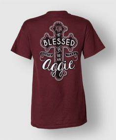 """This funn Aggie tee is perfect for the girl who feels truly blessed to be a Fightin' Texas Aggie! On the front is a small Texas with """"Fightin' Texas Aggies"""" running across the Texas and the back has a large cross with a block ATM at the top and """"Blessed to be an Fightin' Texas Aggie"""" down the cross."""