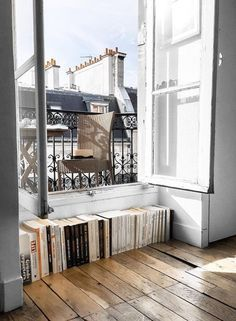 parisian apartment with open windows and books stacked under it
