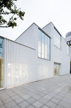 Completed in 2016 in Shanghai, China. Images by Peter Dixie, Leiii Zhang . Commissioned by CaoHeJing in Schmidt Hammer Lassen architects' proposal was to overclad and unify the existing rendered concrete facade. Metal Facade, Metal Cladding, Concrete Facade, Metal Buildings, Office Buildings, Architecture Design, Industrial Architecture, Architecture Office, Facade Design