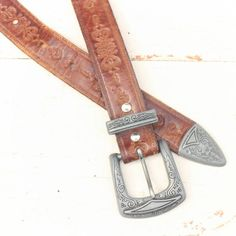"""The women's tooled leather belt is a western style, thinner strap for a nice feminine look. Perfectly worn, solid shape. INTERNATIONAL BUYERS READ SHIPPING POLICIES & FAQ's AT BOTTOM OF PAGE PRIOR TO PURCHASE  Length  from top of strap, at first & last hole - 27 1/2"""" & 31 1/2"""" Width - 7/8""""  Buckle 1 Western Belts, Western Style, Tooled Leather, Leather Tooling, Solid Shapes, Feminine, Nice, Top, Accessories"""