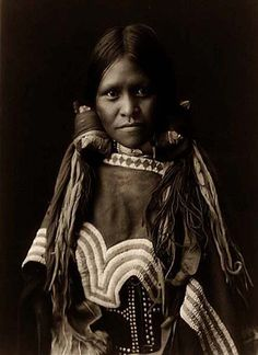 A Young Jicarilla Indian Girl. It was created in 1904 by Edward S. Curtis. She has long dark hair, and is wearing traditional clothing