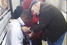 Older man gives heartwarming necktie lesson in train station.