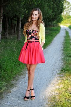 Pale yellow cardigan, a black floral bustier, a coral skirt, and black wedges.