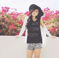 City black tank top, white cardigan, floral pattern flowy shorts, and a black floppy hat