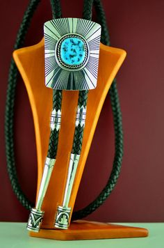 "This exquisite sterling silver overlay Sleeping Beauty Turquoise Bolo Tie is intricately designed and handmade by renowned silversmith Tommy Singer, Navajo. Overlay is 2 pcs of sterling silver cut out and soldered together. The bolo measures 2-7/8"" tall by 2-1/4"" wide. The Sleeping Beauty stone measures 1-1/8"" tall by 1"" wide, set in a scalloped bezel surrounded by a rope design. http://www.twodogssouthwestgallery.com/unique-jewelry/Large-Tommy-Singer-Bolo-Tie/"