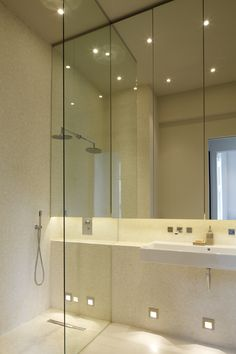 Mirrored bathroom to make the small space look bigger, and a continuous ledge throughout for additional shelving