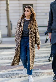 Miroslava Duma wearing a coat with leopard print denim jeans and white sneakers outside Balmain during the Paris Fashion Week Womenswear Fall/Winter...