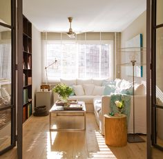 salon con sofa rinconero blanco y puertas de hierro y cristal para acceder 1280x1251