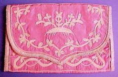 Small 18th century pink silk pocket case (c. 1780-1800) with a beige embroidered flower, leaf and vine design.