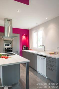 Grande cuisine équipée. Blanche et grise en majorité, certains murs sont couleur fuschia.