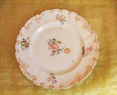 Hullámos formákkal, gazdag aranyozással készült, kifejezetten szép állapotú Geschützt porcelán dísztányér. Arany szegéllyel ellátott, melyet az idő néhol megkoptatott.    Az 1900 – as évek első feléből, gyönyörű virágcsokor motívummal készített ékes darab. Korának megfelelő, zöld porcelánjelzéssel ellátott, 24 cm átmérőjű dísztányér.