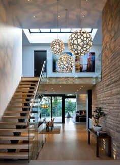 the entryway adorn with three pretty pendant lights, wooden bench with beautiful bonsai on it and stairs with glass railing