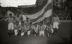 Los jugadores de la Real Sociedad posan con la bandera confeccionada por unas jóvenes con donativos populares antes del primer partido Real Sociedad-Pasaiako. 7 de Octubre de 1928. Fototeka Kutxa