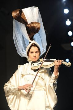 Apparently walking down the runway is not enough anymore. A model balances a violin, an extreme hairdo, and walking the Jean-Paul Gaultier Haute Couture Fall 2011 show during Paris's Couture Fashion Week.