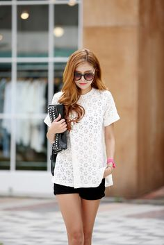 Floral patterned white shirt with shorts and a black studded clutch. Those shades are really chic.