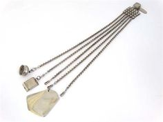 A silver plate housekeepers chatelaine , the 5 strand chains suspending aide de memoire, stamp case etc.