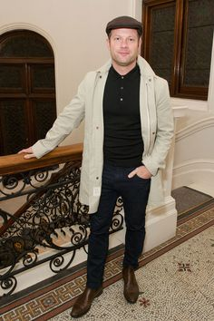 One way to keep dry around town is with a stylish, light raincoat. Dermot O'Leary slips into his at the Lou Dalton x Jaeger presentation.