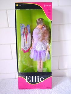 Japanese ELLIE in Lavender Dress with Faux Fur Stole (1991) by Takara. $64.99. Made in Japan. This Ellie doll wears a drop waist lavender dress with a light lavender top with long sleeve silver lace overlay and dark lavender double nylon wide trim bottom.  Ellie wears white thigh high stockings, comes with sparkling silver jelly heels, a lavender faux fur stole,large bud gold earrings and a gold ring.