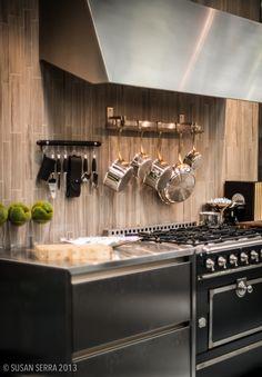www.stainlesssteeltile.com loves the modern kitchen design- wood backsplash, stainless steel hood, and back stove- The Kitchen Designer