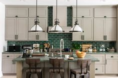 Introducing the HGTV® Dream Home 2017! Peek inside this Southern-inspired seaside home, furnished by Wayfair. The eat-in kitchen is perfect for entertaining, with generous seating at the island and a separate breakfast table. Gray-beige Shaker cabinets keep the focus on the speckled green marble countertops and glass subway tile backsplash. Curved wicker chairs soften the hard lines of the kitchen, while incorporating more natural materials.