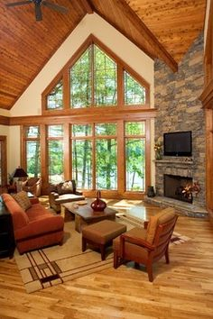 Love the window wall and the fire place in the corner so the furniture can be angled to the windows by day and fire by night!  Don't like the wood plank ceiling