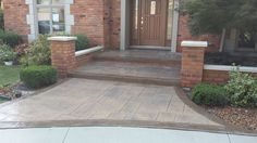 Brick wall build with stamped concrete porch cap and sidewalk. Cement driveway.