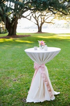 Simple cocktail table with pink ribbon ties, bud vases of dahlias + astilbe, and mercury glass votive candles // Romantic Pink, Peach + Sea Green Wedding at Oak Point Plantation on the Stono in Charleston SC // Dana Cubbage Weddings // Charleston SC + Destination Wedding Photographer