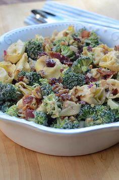 Tortellini Broccoli Salad     1 (12 ounce) package refrigerated cheese tortellini     5 slices thick sliced bacon     2 crowns fresh broccoli, cut into bite size pieces (approximately 4 cups)     1/3 cup red onion, diced     1/2 cup dried cranberries     1/3 cup light mayonnaise     1/3 cup light sour cream     1 tablespoon balsamic vinegar     1 tablespoon white sugar     1/3 cup chopped walnuts